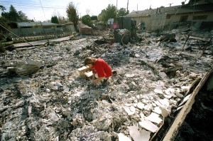 a woman sift through the remain of her burnt house after earthquake